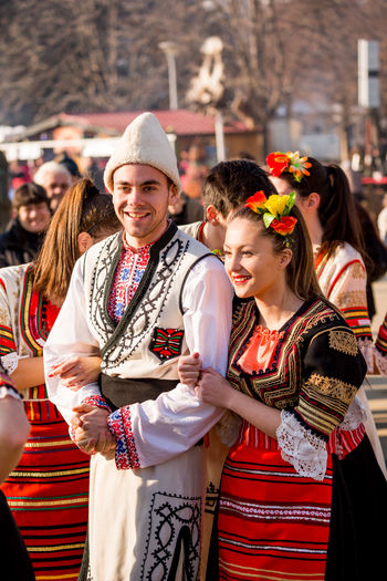 PERNIK, BULGARIA - JANUARY 26, 2018: Couple young dancers in Bulgarian folklore costumes hold arms and laugh at the sunny winter day at the annual International Festival of Masquerade Games Surva Event Games Kukeri Kukeri, Bulgaria Adult Adults Only Celebration Cheerful City Day Festival Flower Friendship Happiness Incidental People Lifestyles Looking At Camera Masquerade Outdoors People Portrait Real People Smiling Standing Surva Togetherness Women Young Adult Young Women