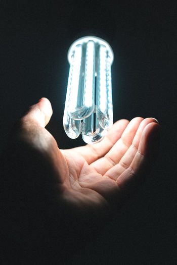 Close-up of hand holding light bulb against black background