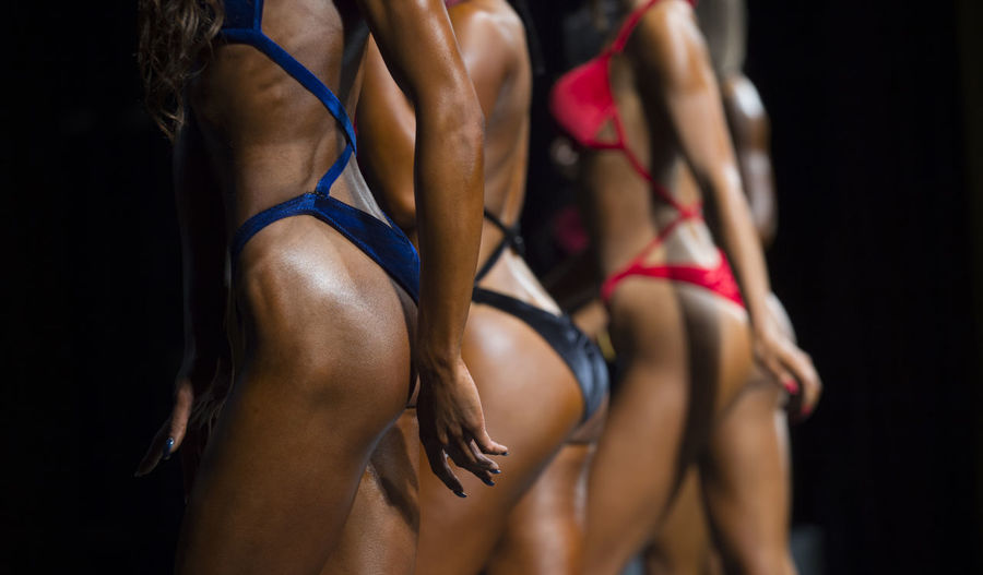 Woman in swimsuits competition fitness bikini. Bodybuilding sport. Strong woman Bodybuilding Bodybuildingmotivation Active Lifestyle  Sports Fitness Healthy Lifestyle Exercising Clothing Human Body Part Strength Women Athlete Young Adult Lifestyles Muscular Build Adult Body Part Sport Sports Training Limb Indoors  Sports Clothing Black Background Young Women Human Limb Human Arm