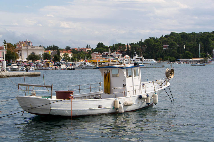 Boats in marina at harbor against sky