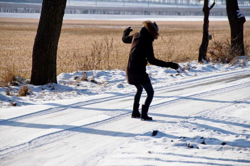 Full length of woman walking on snow covered field