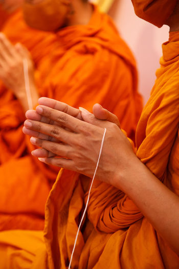 Midsection of man holding orange leaf