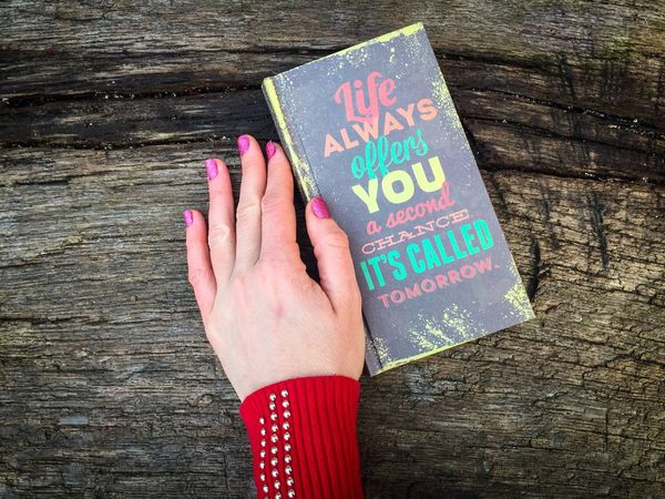 Woman hand with pink nails near a book with a motivational qoute:Life always offers you a second chance it s called tomorrow Human Hand One Person Nail Polish Women Pink Nail Polish Close-up Day People Adults Only Outdoors Adult Words Write Message Qoute  Notes Calendars Life Motivational Book Hand Nails
