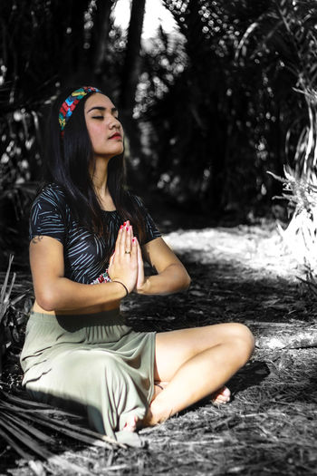 Full Length Of Woman Meditating In Forest