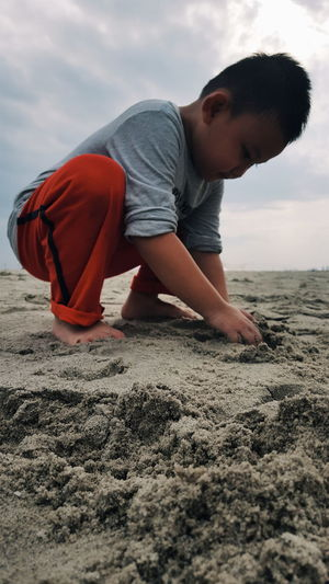 Boy Playing With Sand At Beach Against Sky