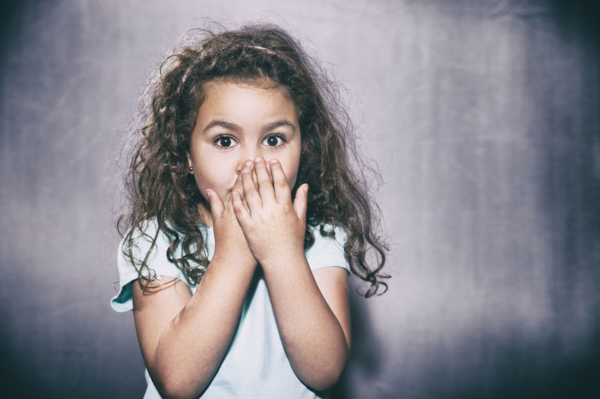 Afraid girl Beautiful People Child Childhood Curly Hair Front View Gray Background Headshot Human Body Part Human Face Human Hand Long Hair Looking At Camera One Person People Portrait Studio Shot