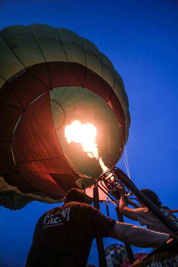 Adventure Air Vehicle Balloon Blue Clear Sky Day Holding Hot Air Balloon Leisure Activity Lifestyles Low Angle View Men Nature Outdoors People Real People Rear View Sky Sunlight