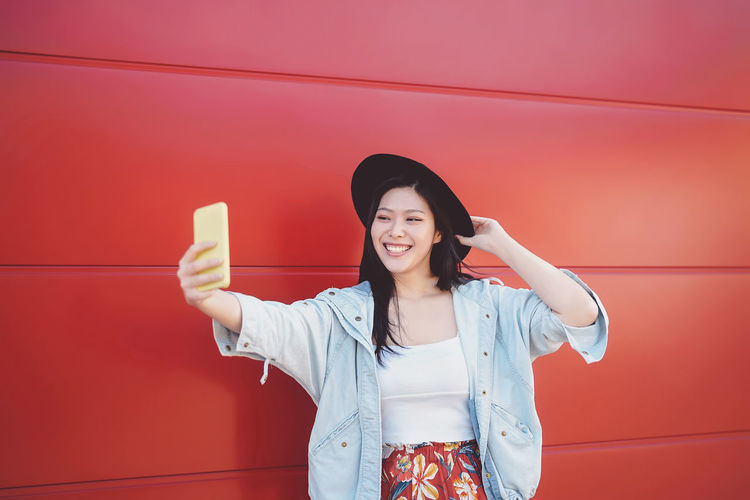 Smiling young woman taking selfie while standing by red wall