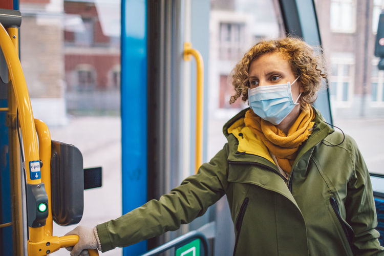 Woman wearing mask standing in bus