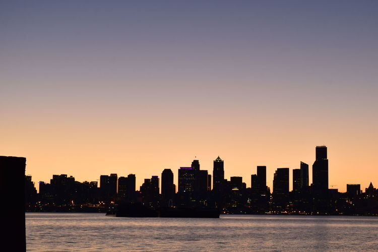 Sea by silhouette buildings against clear sky during sunset