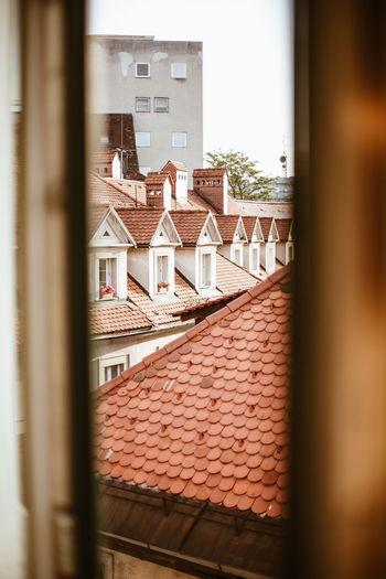 Houses against sky seen through window