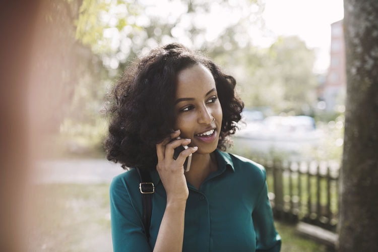 Portrait of young woman using mobile phone outdoors