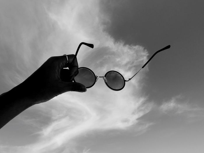Low angle view of hand holding sunglasses against sky