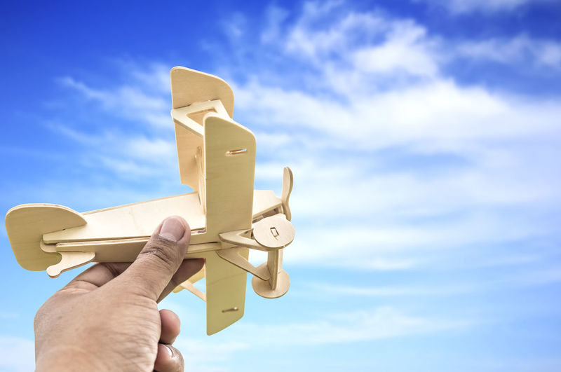 Cropped hand holding model airplane against cloudy sky