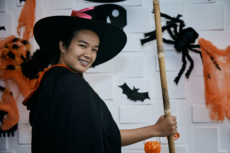 Side view portrait of smiling young woman wearing witch costume while standing at home during halloween