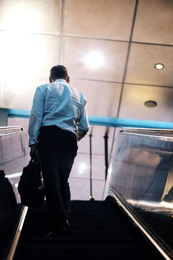 Rear view of man standing on escalator at airport