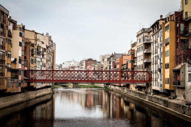 Footbridge over river amidst buildings