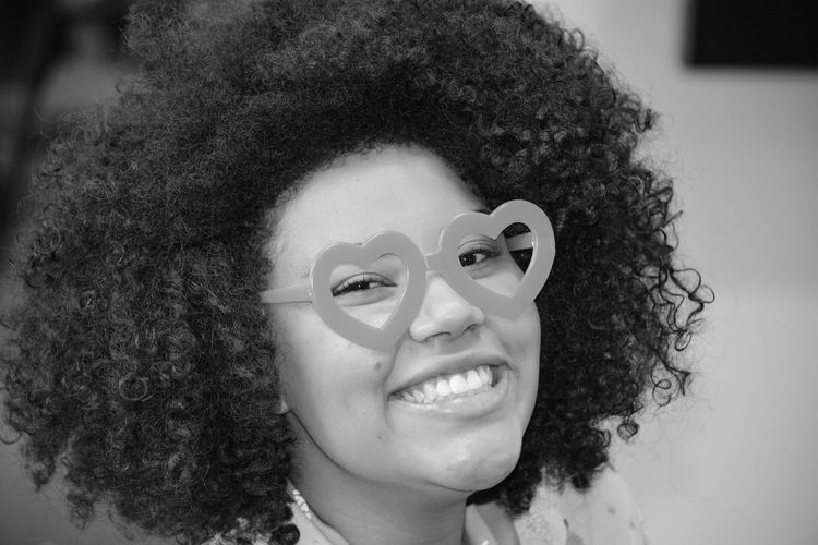 Close-Up Portrait Of Smiling Woman With Curly Hair Wearing Novelty Glasses At Home
