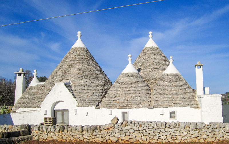 Group of Trulli, traditional old houses and old stone wall under blue sky in countryside, Puglia, Italy Alberobello Ancient Holiday Puglia Roof South Italy Wall Wonderful Architecture Building Exterior Built Structure Italy Monumental  Old Houses Outdoors Salento Spirituality Spring Stone Stone Wall Summer Trulli Trullo Valle D'itria Wonderful Day