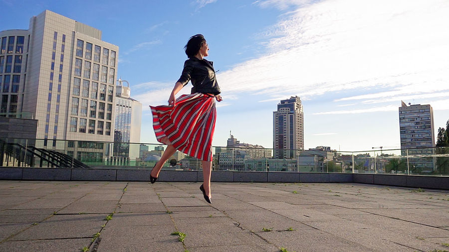 Rear view of woman standing by cityscape against sky