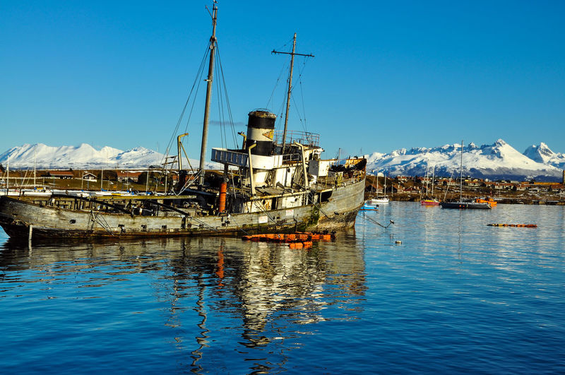Old boat moored in harbor at beagle channel against clear blue sky