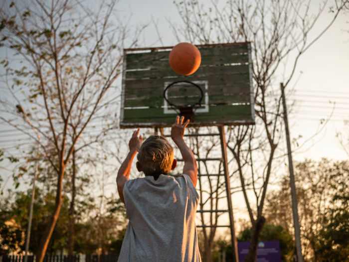 Rear view of senior man playing basketball at sunset