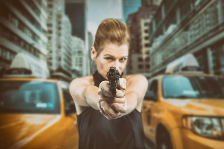 City Crime Woman Woman Power Buildings City Cty Streets Day Front View Gun Handgun Holding One Person Outdoors People Perspective Photography Real People Scene Scenery Standing Streetphotography Weapon Woman Portrait Yellow Cab