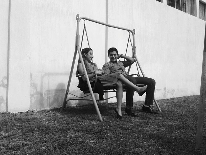 Full length of man and woman sitting on swing by wall