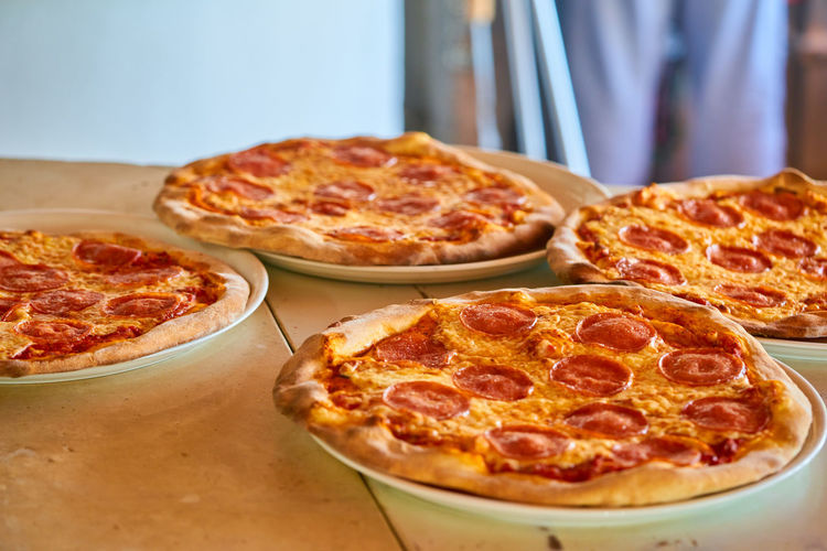 Cheese Dairy Product Fast Food Focus On Foreground Food Food And Drink Freshness High Angle View Indoors  Indulgence Italian Food No People Pepperoni Pepperoni Pizza Pizza Pizzeria Ready-to-eat Sausage Snack Still Life Table Tomato Sauce Unhealthy Eating