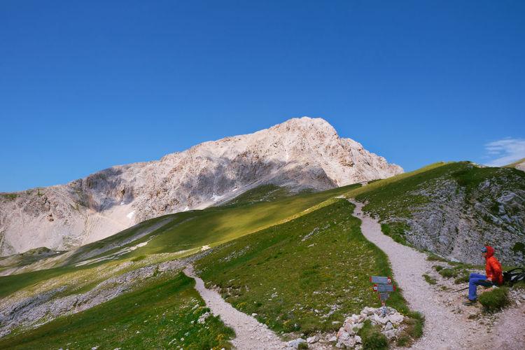 Hiker in the path and in the background the gran sasso d'italia abruzzo