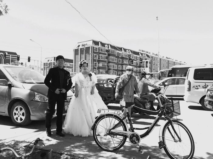Car Transportation Mode Of Transport Land Vehicle Bicycle Bride Men Real People Women Building Exterior Togetherness Wedding Wedding Dress Street Built Structure Architecture Clear Sky Outdoors City Day