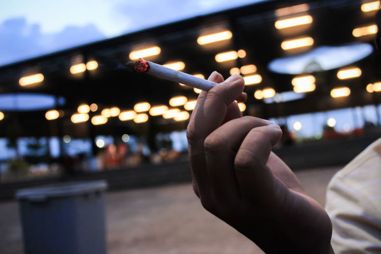 Cropped Hand Of Man Holding Cigarette In Illuminated City