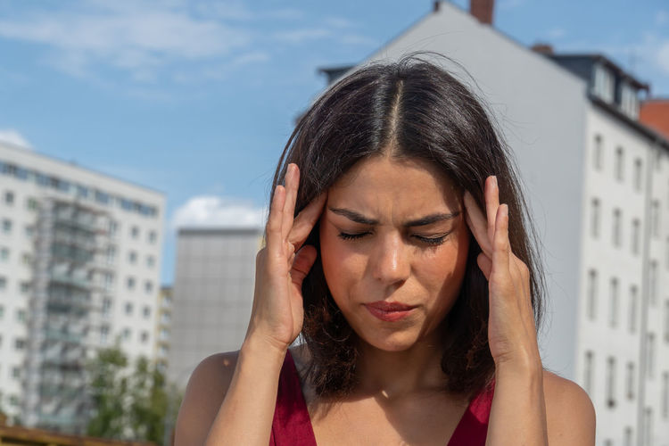 Close-up of woman with headache standing in standing in city