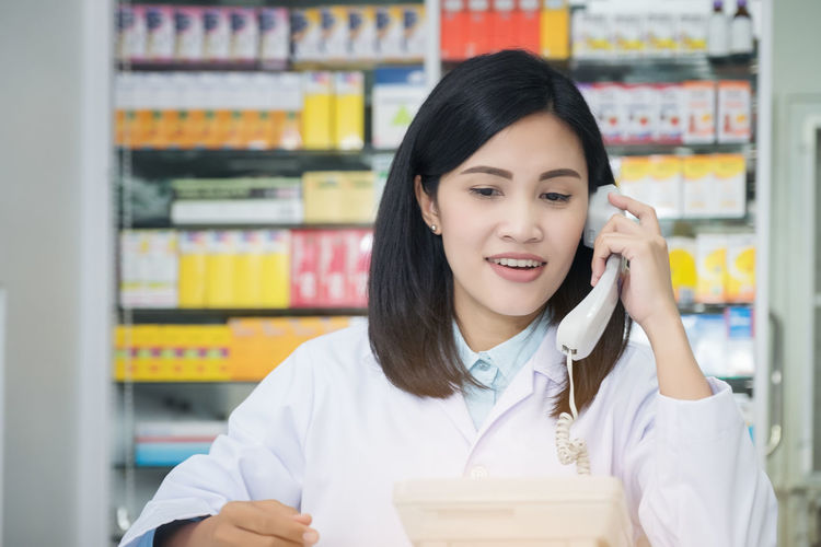 Pharmacy worker talking by phone, Attractive young smiling female at desk with telephone to ear Front View Indoors  Shelf One Person Holding Focus On Foreground Portrait Occupation Young Adult Waist Up Adult Healthcare And Medicine Standing Communication Smiling Store Young Women Real People Lab Coat Hairstyle