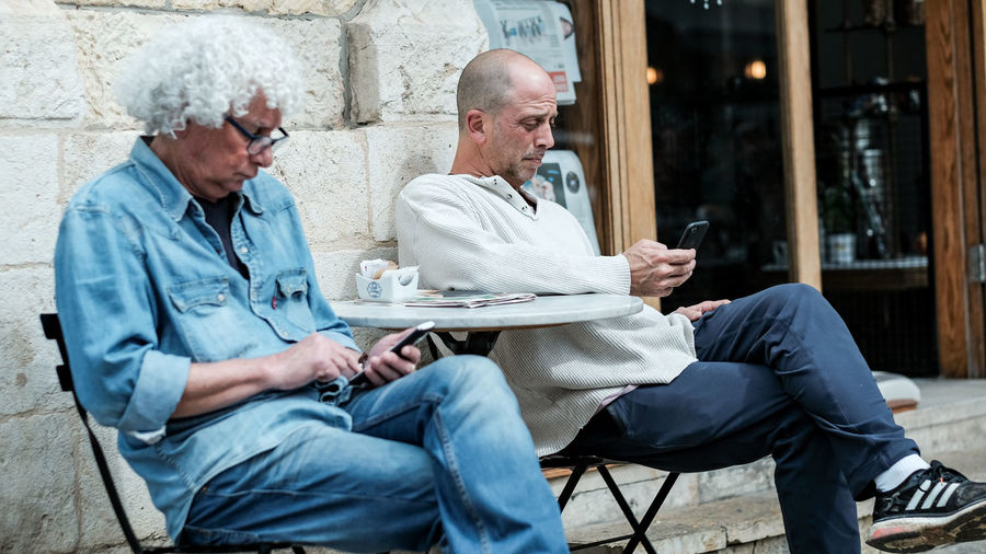 Friends sitting on mobile phone in restaurant