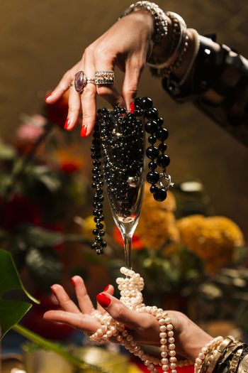 Gestures of a woman with jewelry, pearls, fruits and flowers. Abundance Wealth Celebration Art And Craft Mood Jewelry Gold Pearls Gesture Luxury Human Hand Hand Human Body Part One Person Focus On Foreground Holding Real People Adult Human Finger Finger Women Food And Drink Wine Body Part Ring Bracelet Food Close-up Glass Nail