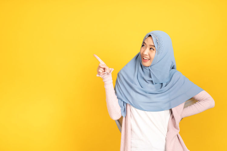 Mid adult woman standing against yellow background