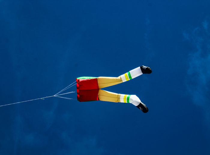 Low angle view of kite flying against blue sky