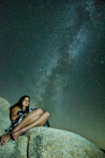 Teenage girl sitting on rock against star field
