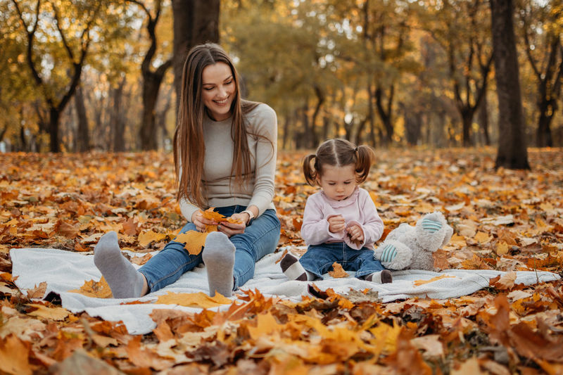 Happy woman with autumn leaves against trees