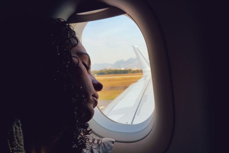 Airplane Car Interior Carla Balbi Close-up Cropped Curly Hair Day Glass - Material Journey Landscape Lazy Leisure Activity Lifestyles Mode Of Transport Part Of Ricardo Barbosa Sky Sleep Transportation Travel Trip Vehicle Interior Window Windshield Wing The Traveler - 2018 EyeEm Awards