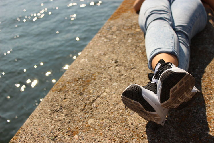 Low section of man wearing shoes relaxing on retaining wall by sea
