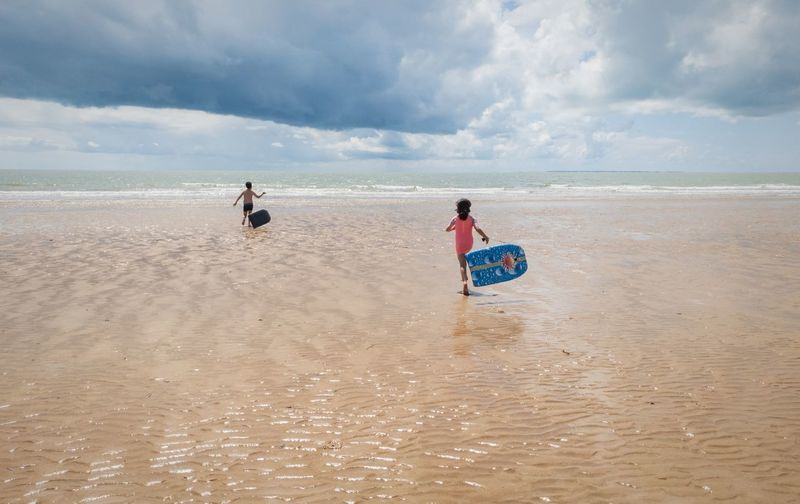 Rear view of children holding pool rafts while running towards sea against cloudy sky