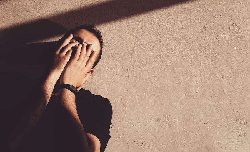 Low angle view of man covering face while standing against wall