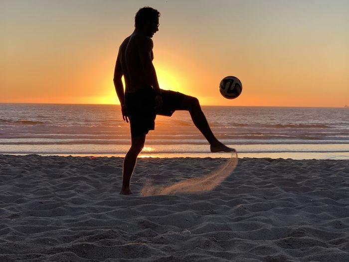 Shirtless man kicking ball at beach against sky during sunset