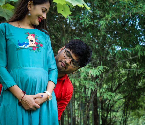 Man looking at pregnant woman abdomen against tress in forest