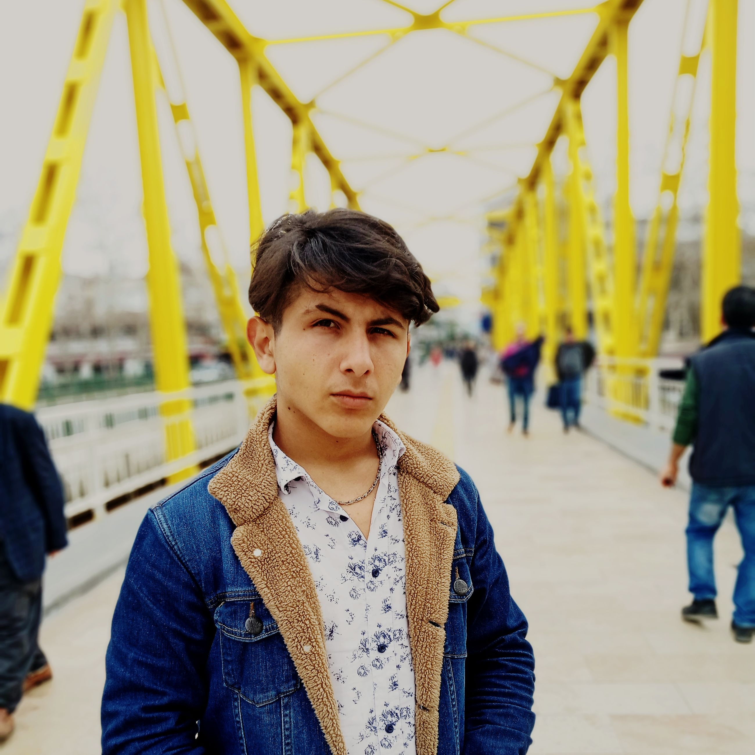 one person, young adult, portrait, focus on foreground, young men, real people, front view, looking at camera, leisure activity, casual clothing, clothing, incidental people, lifestyles, standing, jacket, handsome, architecture, day, yellow, outdoors, scarf, hairstyle
