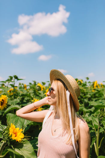 Woman with straw hat standing in the sunflower field