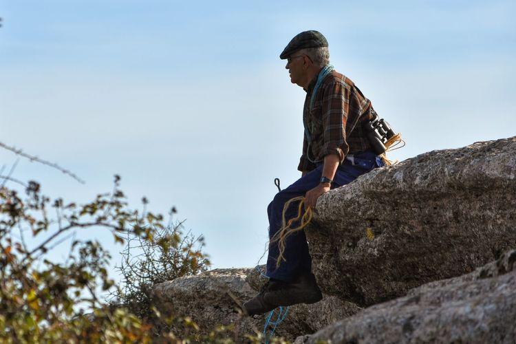 Mature man sitting of rock against sky