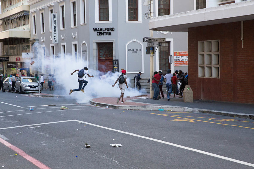 A student jumps over stun grenade smoke as police disperse protestors from the Fees Must Fall movement outside Parliament's gates. 28th October 2016 Cape Town Feesmustfall Police Car South Africa The Photojournalist - 2017 EyeEm Awards The Photojournalist - 2017 EyeEm Awards